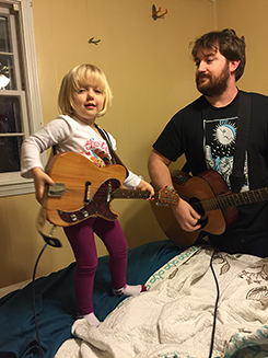 a scraggly doofus playing guitar while a young child plays electric mandolin on a bed